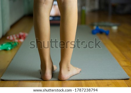 Legs on a sports mat next to sports equipment. Jump rope, ruler, dumbbells, scales. Online training at home. Fitness at home.