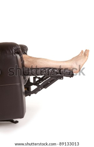 Legs raised on a new leather recliner chair isolated on a white background
