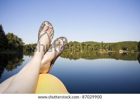 Legs resting on a paddle boat in calm lake water shot in muskoka cottage country ontario - stock photo