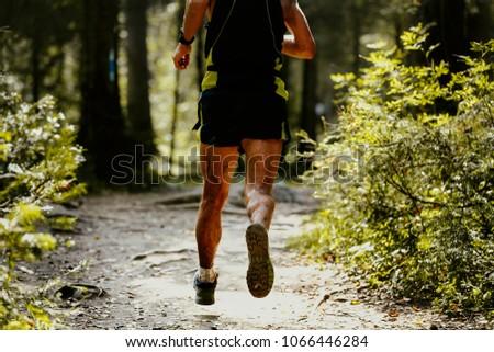 legs runner athlete in spray dirt forest trail run #1066446284