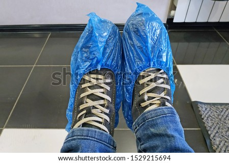 Legs shod in boots and blue shoe covers. Shoe covers on the legs close-up. Legs in shoe covers against the background of the floor covered with ceramic tiles. Sanitary standards in the hospital. #1529215694