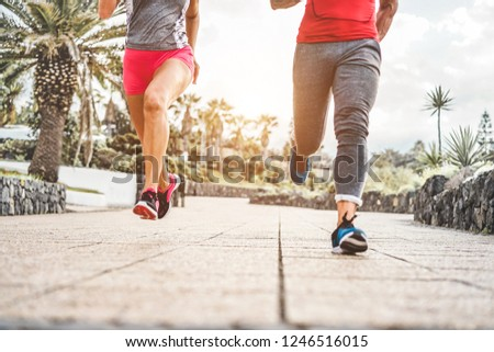 Legs view of fitness friends running outdoor - Joggers people training at evening time after work - Jogging, healthy lifestyle and sport concept - Main focus on woman back foot #1246516015