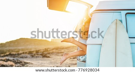 Legs view of happy surfer girl inside minivan at sunset - Young woman having fun on summer vacation - Travel,sport and nature concept - Focus on feet - Warm contrast filter