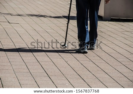 Legs walking with walking sticks and shadows