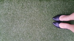 Legs with black high heel shoes on green grass with copy space