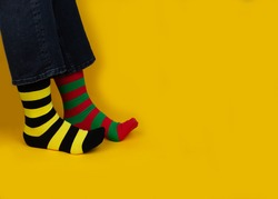 Legs with different stripes socks on background with copy space. World Down syndrome day background. Down syndrome awareness concept.