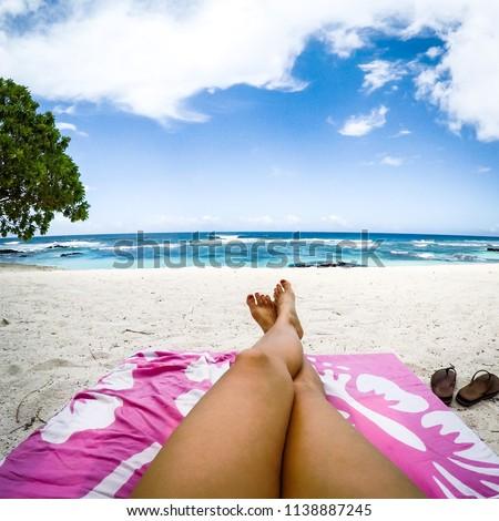 Legs with fake spray tan on sun lounger on tropical beach with pink towel at Lefaga, Upolu Island, Western Samoa, South Pacific #1138887245