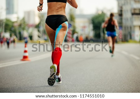 legs woman runner in red compression socks and blue kinesio tape on thigh #1174551010