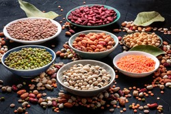 Legumes assortment on a black background. Lentils, soybeans, chickpeas, red kidney beans, a vatiety of pulses