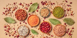 Legumes assortment, overhead panoramic shot on a brown background. Lentils, soybeans, chickpeas, red kidney beans, black-eyed peas, a vatiety of pulses