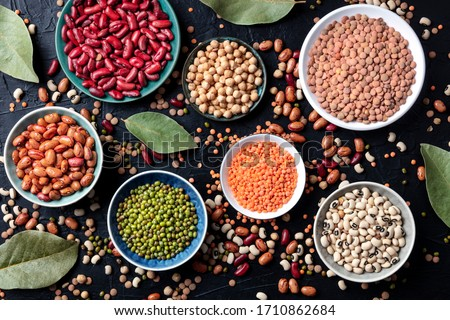 Photo of  Legumes assortment, shot from the top on a black background. Lentils, soybeans, chickpeas, red kidney beans, a vatiety of pulses