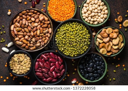Legumes, lentils, chikpea and beans assortment in different bowls on stone table. Top view.