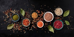 Legumes panorama, shot from the top on a black background. Lentils, soybeans, chickpeas, red kidney beans, a vatiety of pulses