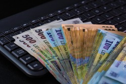 Lei banknotes on keyboard. Selective focus on stack of LEI romanian money.