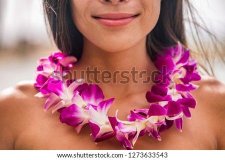 Lei hawaii welcome necklace of fresh orchids flowers garland on woman's neck. Aloha spirit. Hula dancer at luau beach party.