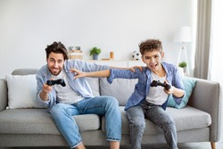 Leisure activities concept. Joyful father and son competing in playing video games, pushing each other while sitting together on sofa in living room. Stay at home with fun