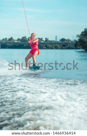 Leisure activity. Vertical shot of an active Caucasian woman riding a wakeboard on a local river enjoying her leisure time