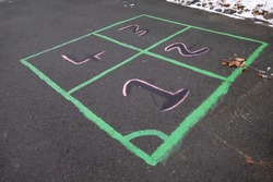 Leisure and creative childhood game of four squares. The colourful squares are outlined using green caulk and the numbers are black and pink in colour. The outdoor children's game is on black asphalt