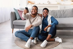 Leisure And Entertainment. Smiling African American couple watching TV show or film, guy holding remote control. Young man and woman enjoying free time sitting on floor carpet at home in living room
