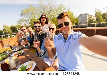 leisure and people concept - happy friends having bbq party on rooftop in summer and taking selfie