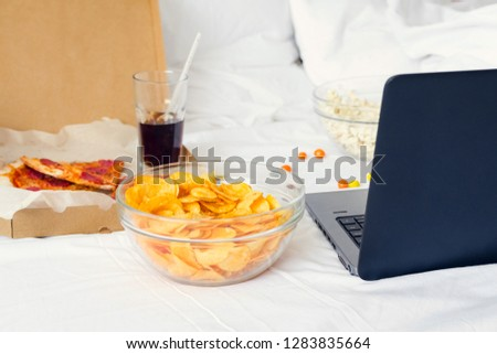 Leisure at home with laptop and fast food on weekend. Fastfood snacks: pizza, popcorn, potato chips, candies and computer on the bed. Bad habits concept. Unhealthy Lifestyle. #1283835664
