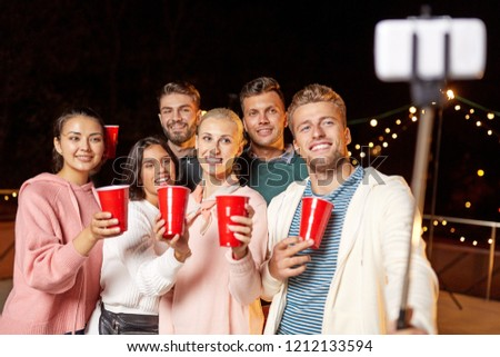 leisure, celebration and people concept - happy friends with drinks taking picture by selfie stick at rooftop party at night