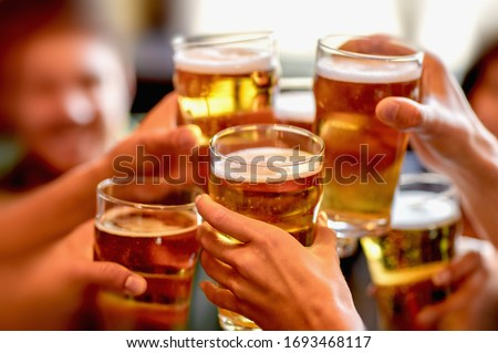 leisure, drinks, celebration, people and holidays concept - smiling friends drinking beer and stitching glasses in a restaurant or pub