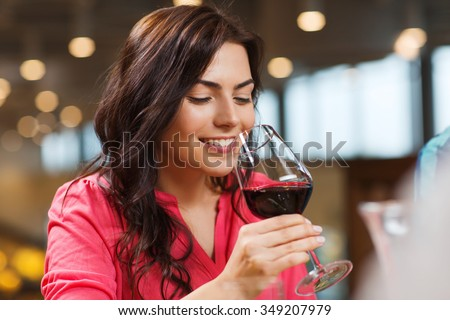 leisure, drinks, degustation, people and holidays concept - smiling woman drinking red wine at restaurant #349207979