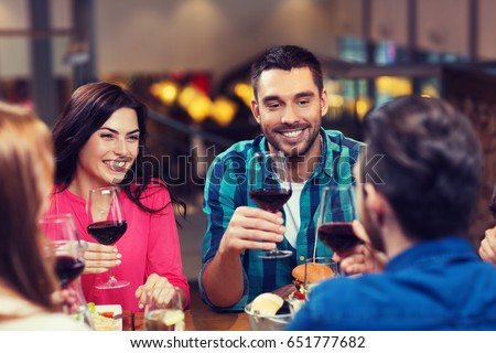leisure, eating, food and drinks, people and holidays concept - smiling friends having dinner and drinking red wine at restaurant #651777682