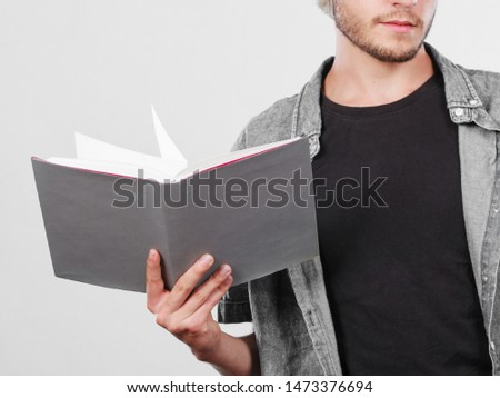Leisure, education, literature concept. Young handsome male student holding textbooks book