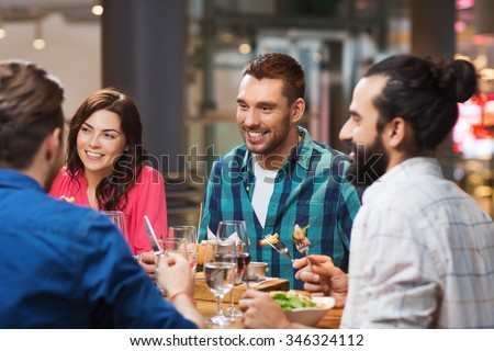 leisure, food and drinks, people and holidays concept - happy friends having dinner at restaurant