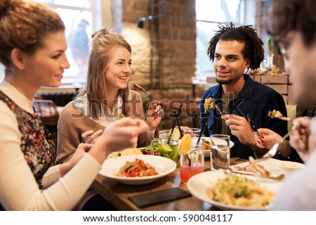 leisure, food, drinks, people and holidays concept - happy friends eating and drinking at restaurant #590048117