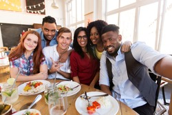 leisure, friendship, people and holidays concept - happy friends taking selfie at restaurant or bar