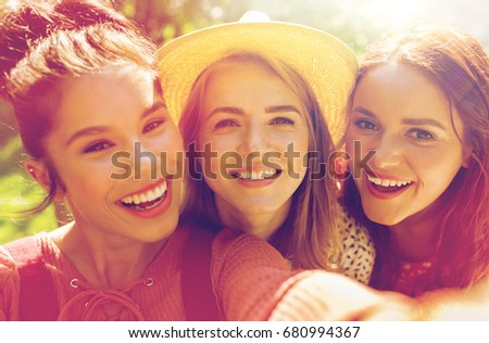 leisure, holidays and people concept - happy women or friends taking selfie at summer