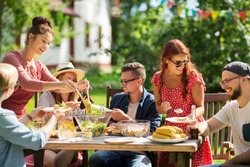 leisure, holidays, eating, people and food concept - happy friends having dinner and sharing salad at summer garden party