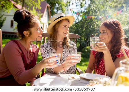 leisure, holidays, eating, people and food concept - happy women or friends with drinks celebrating reunion and having dinner at summer garden party