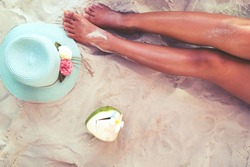 Leisure in summer - Beautiful of sexy women tan. relax on sandy beach with hat and coconut cocktail. vintage color styles