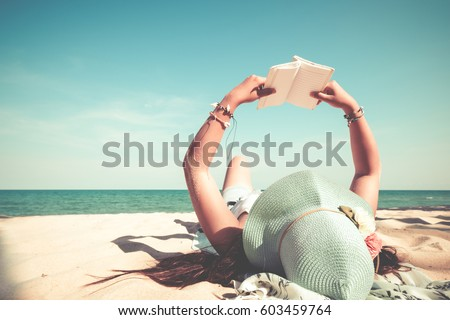 Leisure in summer - Young women lying on a tropical beach, relax with book. Blue sea in the background. Summer vacation concept. vintage color tone. #603459764