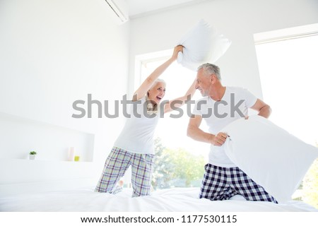 Leisure, lifestyle and happiness concept. Low angle top view of careless grey hair couple in sleepwear, spend time together, make a pillow fight in a middle of white house