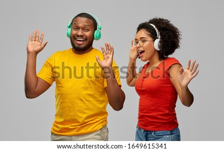 leisure, music and people concept - happy african american couple with headphones dancing over grey background