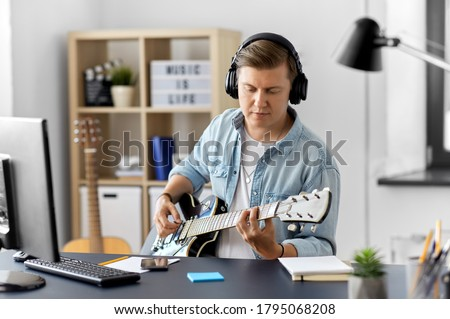 leisure, music and people concept - young man or musician in headphones with computer playing bass guitar sitting at table at home Photo stock ©