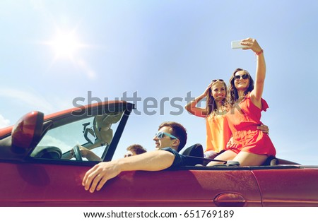 leisure, road trip, travel and people concept - happy friends driving in cabriolet taking selfie by smartphone outdoors #651769189