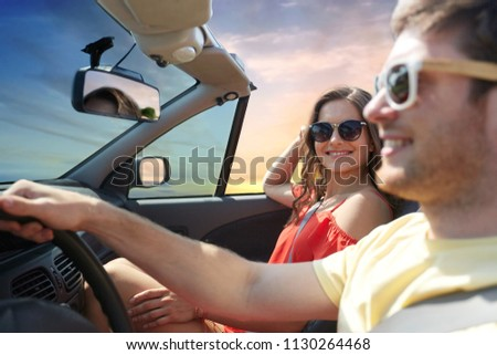 leisure, road trip, travel, summer holidays and people concept - happy couple driving in convertible car over sky background