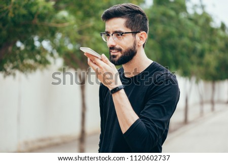 Leisure, technology, communication and people concept - young man using voice command recorder or calling on smartphone at street #1120602737