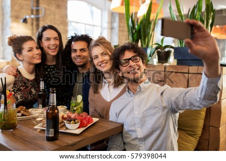 leisure, technology, friendship, people and holidays concept - happy friends with food and drinks taking selfie by smartphone at bar or cafe
