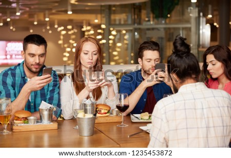 leisure, technology, lifestyle and people concept - friends with smartphones dining at restaurant #1235453872