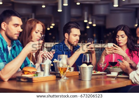 leisure, technology, lifestyle and people concept - friends with smartphones dining at restaurant #673206523