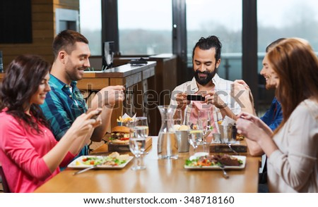 leisure, technology, lifestyle and people concept - happy friends with smartphones taking picture of food at restaurant
