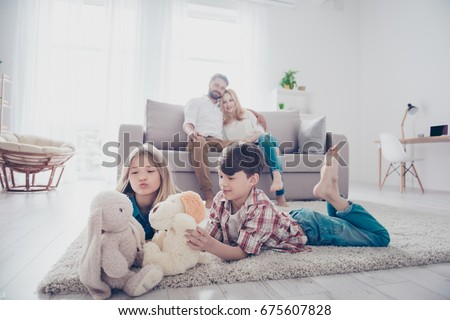 Leisure together. Happy family of four is enjoying at home, small kids are playing with toys, parents are on the sofa, hugging #675607828