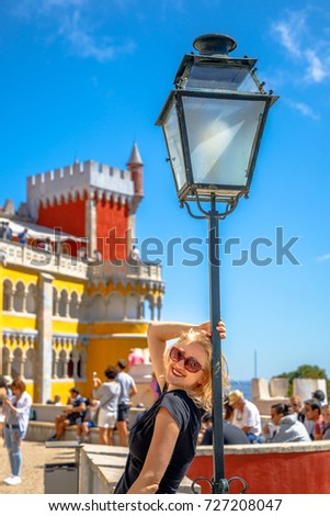 Leisure, travel and tourism concept. Happy caucasian woman posing on a light pole with defocused background. Female traveler visits the biggest tourist attraction of Sintra, Lisbon district, Portugal. #727208047